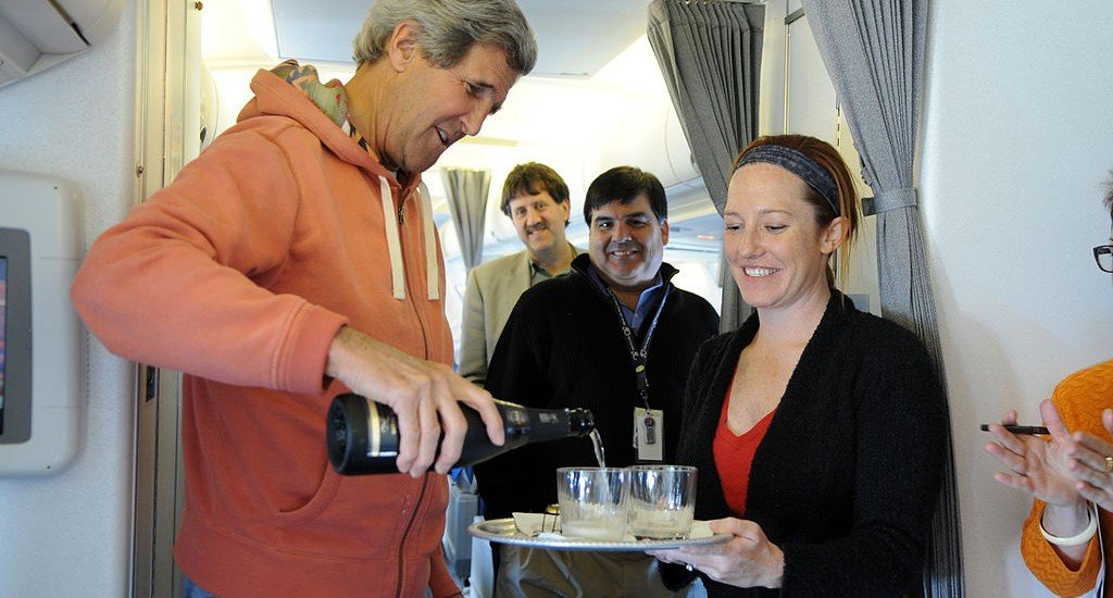 U.S. Secretary of State John Kerry uncorks a bottle of champagne en route from Andrews Air Force Base to Stockholm, Sweden as he celebrates the first press briefing at the U.S. Department of State Department by his new Spokesperson, Jen Psaki, on May 13, 2013. (US Department of State)