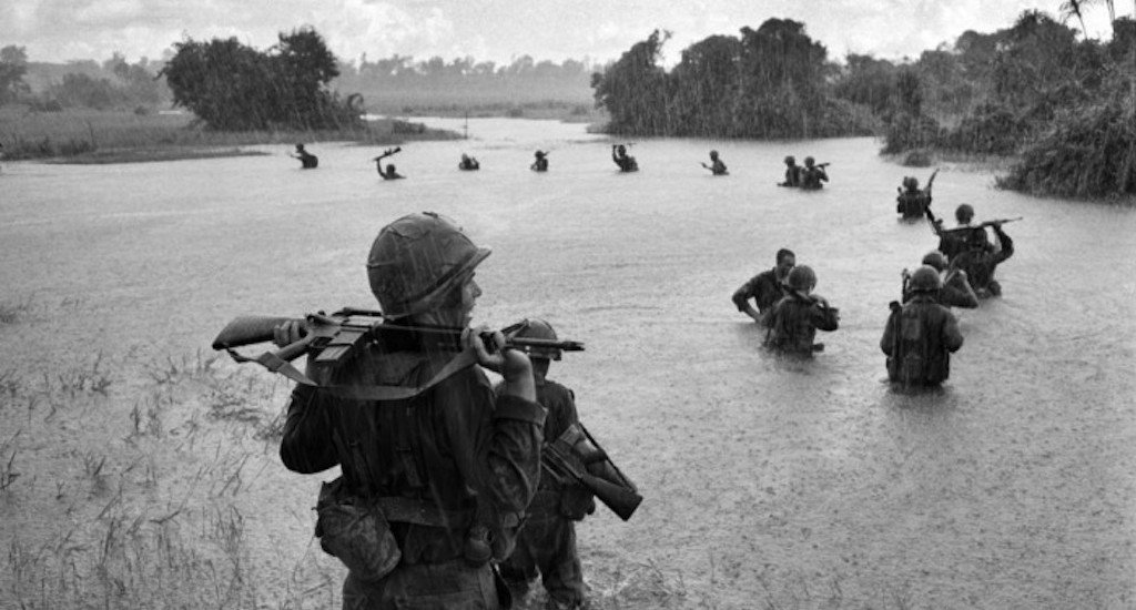 US paratroopers of the 2nd Battalion, 173rd Airborne Brigade, hold their automatic weapons above water as they cross a river in the rain during a search for Vietcong positions in the jungle area of Ben Cat on 25 September 1965. The paratroopers had been combing the area for 12 days with no enemy contact Photograph: Henri Huet/AP