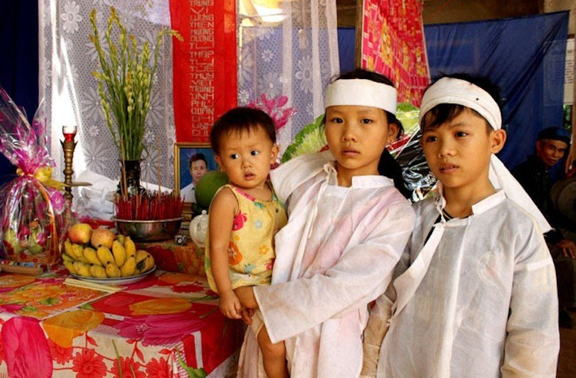 Le Huu Ha's three children, 8-year-old Le Thi Hang at left holding 14-month-old baby sister Le Thi Thuy Trang, and their 12-year-old brother Le Huu Huy, stand by their father's funeral altar.